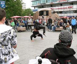 Aus dem Rollstuhl betrachtet Alex die Streetdance-Show am Alex in Berlin