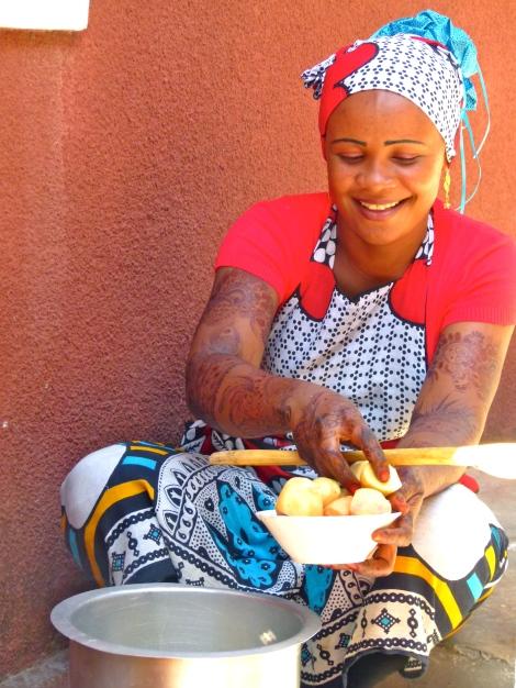 Eine junge Frau mit Henna bemalten Armen kocht in einem Hinterhof