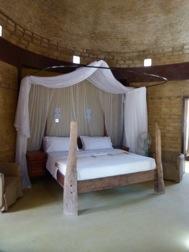 In einer aus Lehmziegeln gebauten Raum mit Kuppel steht ein Himmelbett mit Holzelementen