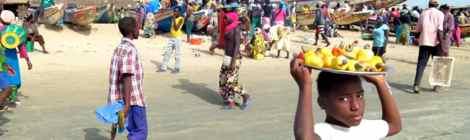 Ein Junge trägt ein Tablett mit Cashewnüssen auf dem Kopf, dahin viele Menschen vor Fischerbooten