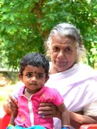 Eine ältere grauhaarige Frau hält ein Kleinkind auf dem Schoß