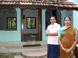 Eine Frau in gelbem Sari und ein Mann mit weißem Hemd stehen vor ihrem Haus