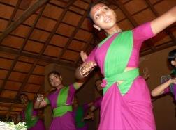 Drei Mädchen in rosa-grünen Saris zeigen synchrone Tanzschritte