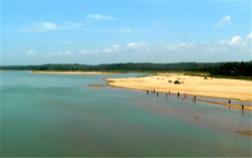 Blauer Fluss mit goldenem Sandstrand und Menschen, die im Wasser stehen