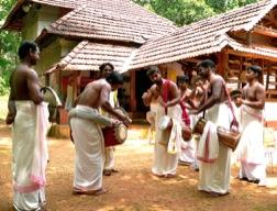 Eine Gruppe Männer mit weißer Beinbekleidung und nacktem Oberkörper spielen auf diversen Blas- und Perkussionsinstrumenten