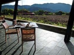 Zwei Stühle und ein gedeckter Frühstückstisch mit Blick über eine Teeplantage und Lodges im Hintergrund