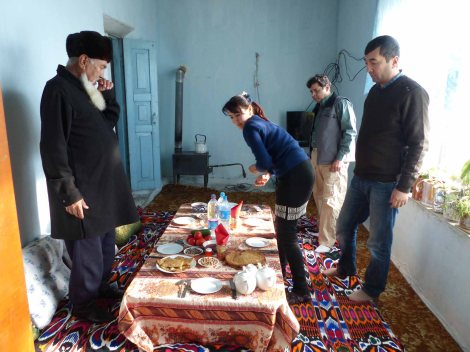 Vier Menschen stehen um einen gedeckten Tisch