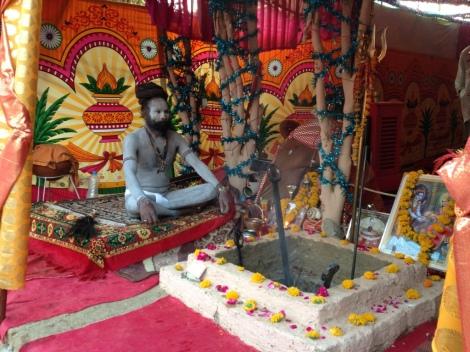 Ein Sadhu meditiert am Morgen vor der Feuerstelle in seinem Zelt