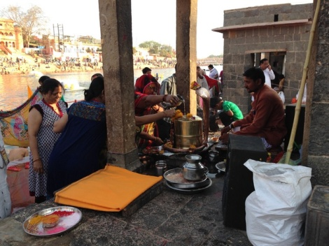 Frauen schütten Flusswasser über einen Lingam, ein Symbol von Gott Shiva