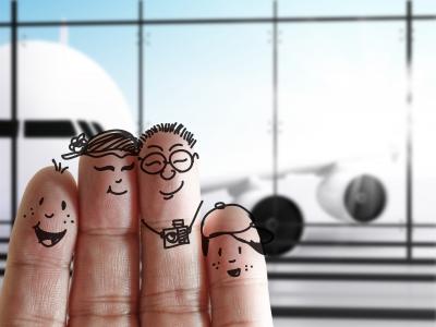 Die ganze Familie gut gelaunt mit Kindern am Flughafen. So sollen Flugreisen sein.